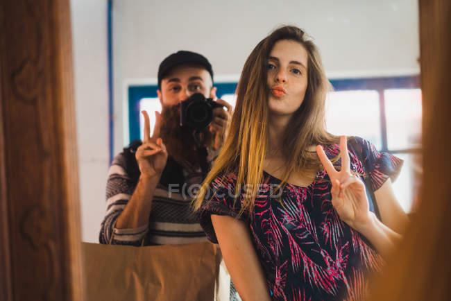 Jeune homme prenant selfie avec femme gesticulant deux doigts à miroir — Photo de stock