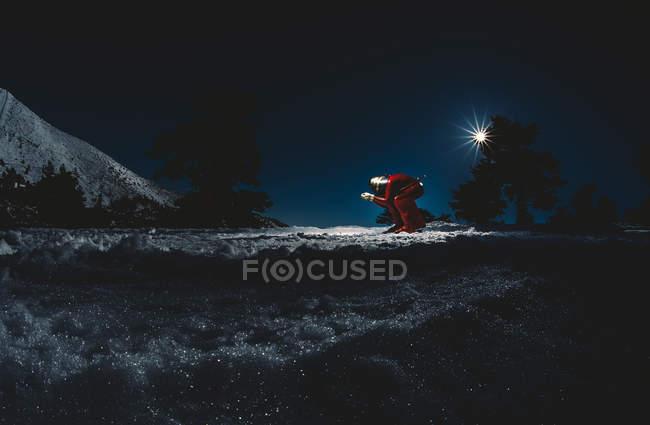 Homem praticando velocidade esquiar numa encosta ao entardecer — Fotografia de Stock