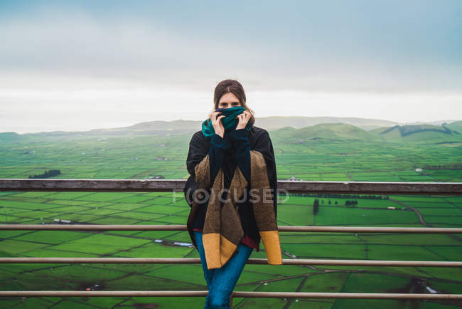 Woman hiding face with scarf and leaning on rural fence on background of amazing panoramic view of misty fields — Stock Photo