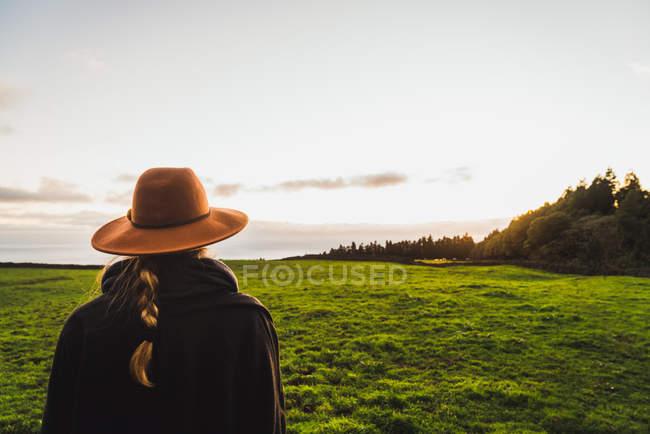 Rückansicht einer Frau mit Hut und posiert vor dem Hintergrund grüner Hügel — Stockfoto