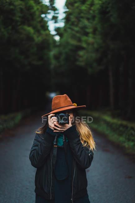 Mulher levando tiro com câmera na estrada na floresta — Fotografia de Stock