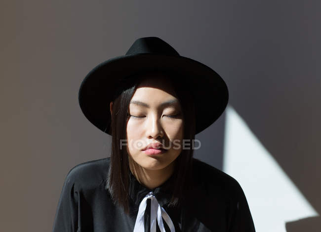 Stylish woman in hat posing with eyes closed — Stock Photo