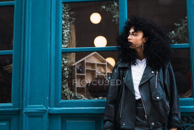 Pretty curly woman posing at window — Stock Photo
