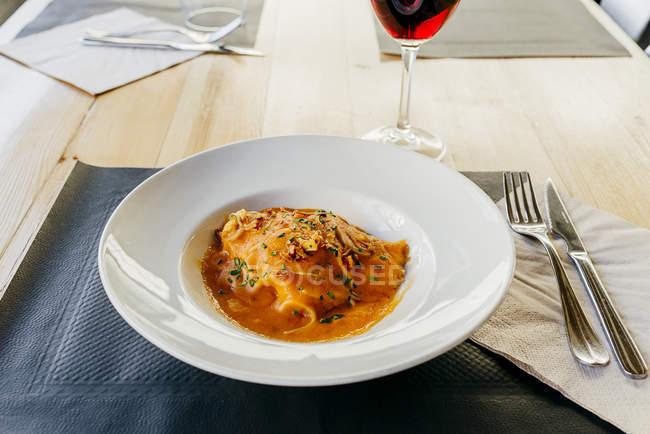 Arrosto di maiale con salsa sul piatto al tavolo — Foto stock
