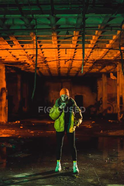 Giovane donna alla moda in rivestimento giallo in piedi e l'utilizzo di smartphone in edificio abbandonato grungy — Foto stock