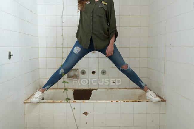 Jeans Vasca Da Bagno : Sezione bassa della donna in piedi sulla vasca da bagno in luogo