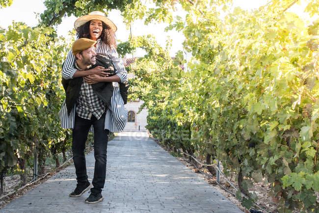 Happy man giving piggy back to girl at sunlit vineyard — Stock Photo
