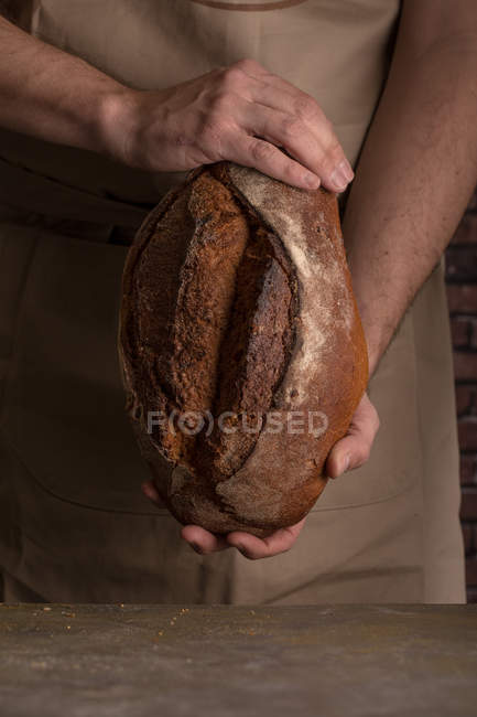 Crop male hands holding freshly baked loaf of bread — Stock Photo