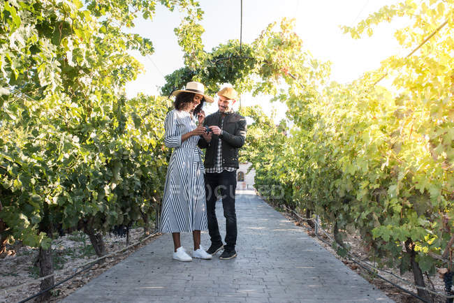 Glückliches Paar verkostet Trauben in Gasse im Weinberg — Stockfoto