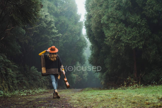 Back view of woman walking with ukulele in rural forest road — Stock Photo