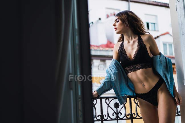 Frau in schwarzen Dessous posiert auf Balkon — Stockfoto