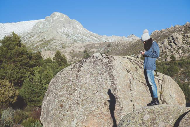 Vista lateral da mulher com o smartphone na rocha em natureza — Fotografia de Stock