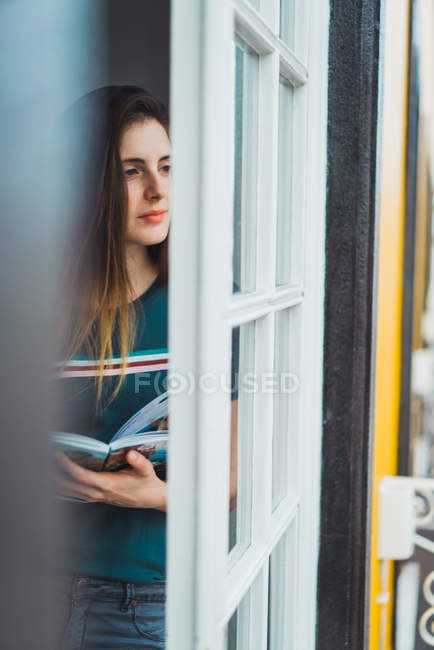 Mädchen mit Buch in Händen wegschauen im Fenster träumen — Stockfoto