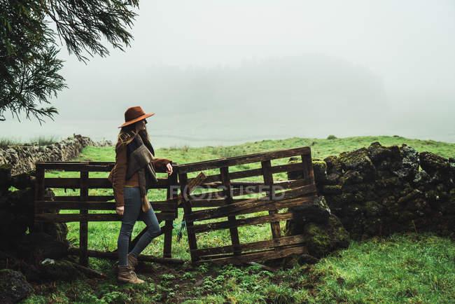 Vista lateral de la mujer en chaqueta y sombrero apoyado en la cerca vieja con campos brumosos en el fondo . - foto de stock