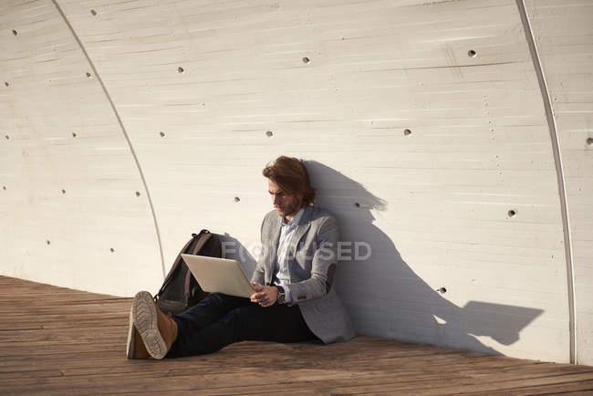 Homme d'affaires assis au passage urbain et utilisant un ordinateur portable — Photo de stock
