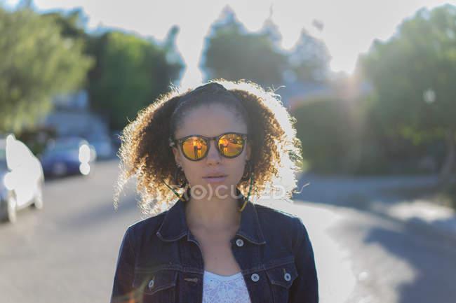 Stylish girl in sunglasses walking at street — Stock Photo
