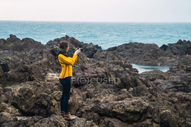 Вид збоку туристичних жінка, стоячи на скелястому узбережжі і прийняття знімків з камери — стокове фото