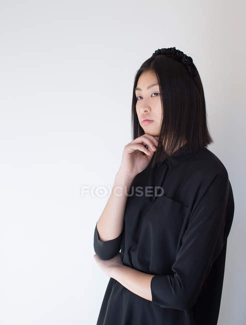 Stylish woman in black posing with chin on hand in studio — Stock Photo