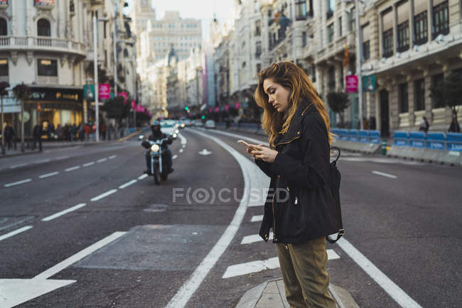 Woman using smartphone on city road — Stock Photo