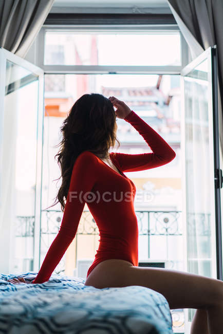 Side view of woman in red swimming suit sitting on bed — Stock Photo