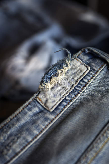 Close up view of teared blue jeans — Stock Photo