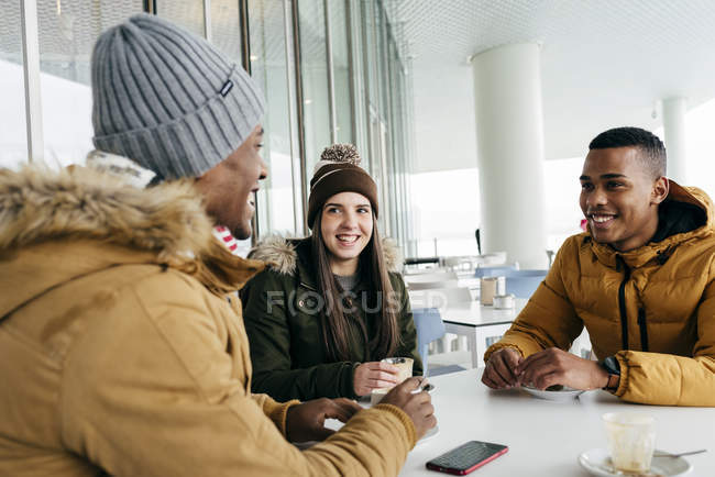 Cheerful friends sitting in cafe and smiling — Stock Photo