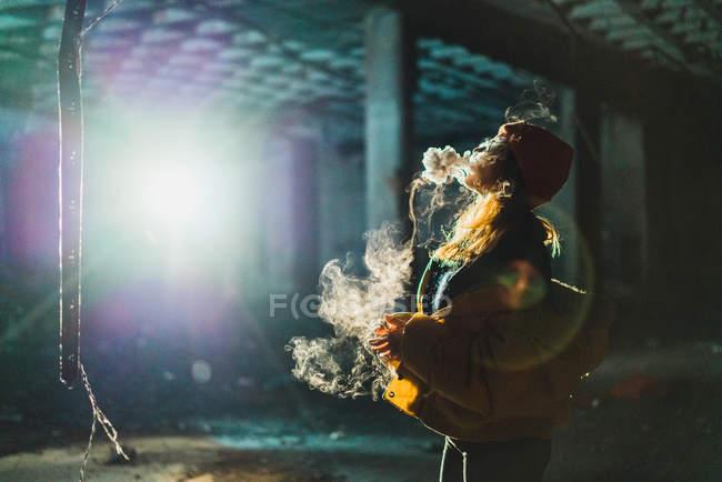 Mujer vapeando en edificio abandonado - foto de stock