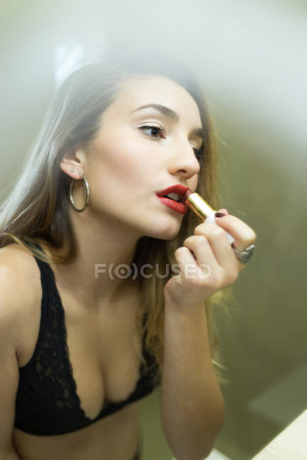 Portrait of young woman painting lips with red lipstick — Stock Photo