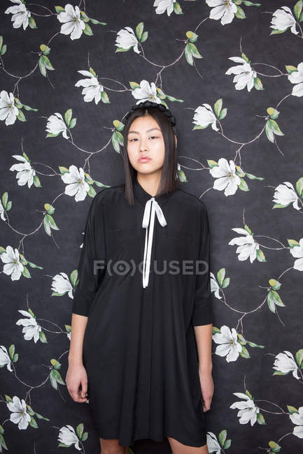 Pretty young woman in black dress looking at camera and posing on on floral backdrop — Stock Photo
