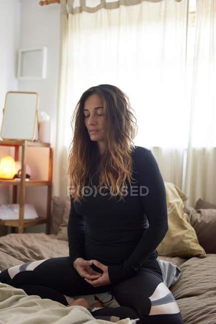 Mulher fazendo exercícios de ioga na cama em casa — Fotografia de Stock