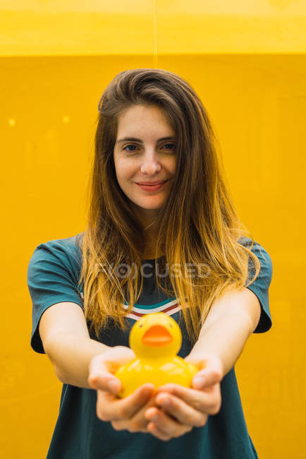 Young girl outstretching hands with yellow rubber duck and looking at camera. — Stock Photo