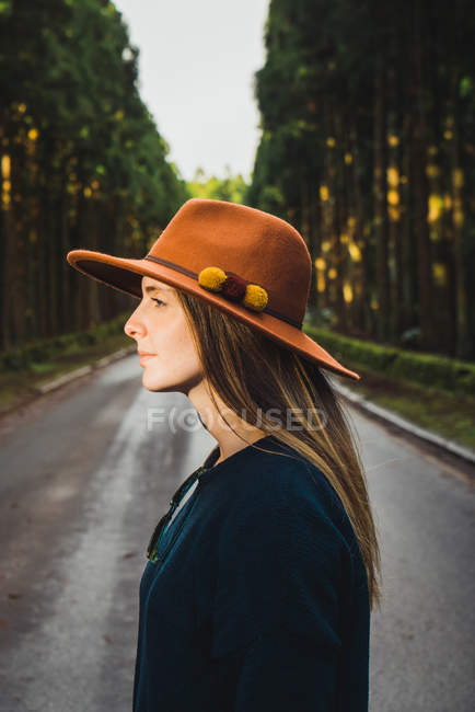 Young woman in hat at sunny forest road — Stock Photo
