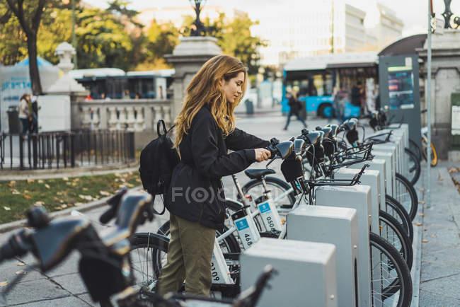 Vue latérale de la femme blonde prenant le vélo dans le parc — Photo de stock