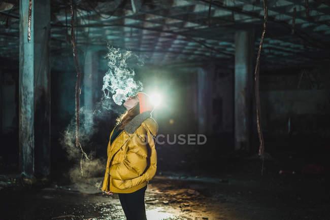 Mujer vapeando en edificio abandonado por la noche - foto de stock