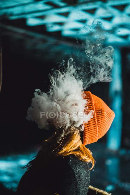 Vista laterale della donna irriconoscibile che sbuffa vapore nell'edificio abbandonato di notte . — Foto stock