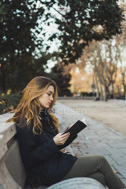 Side view of pretty woman sitting on park bench and reading book. — Stock Photo