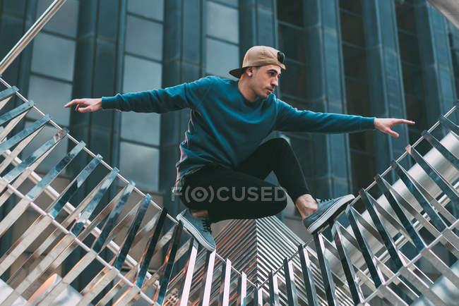 Счастливый человек делает акробатические позы на металлической скульптуре — стоковое фото