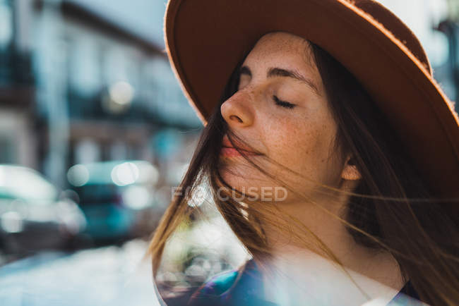 Pretty sensual woman in hat posing with eyes closed on street. — Stock Photo