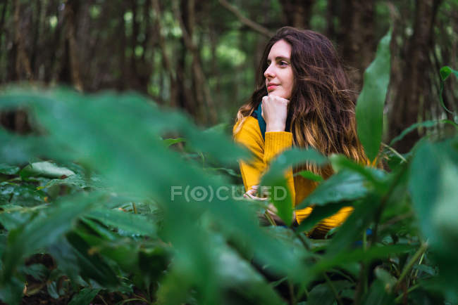 Young woman sitting in green forest and looking away. — Stock Photo