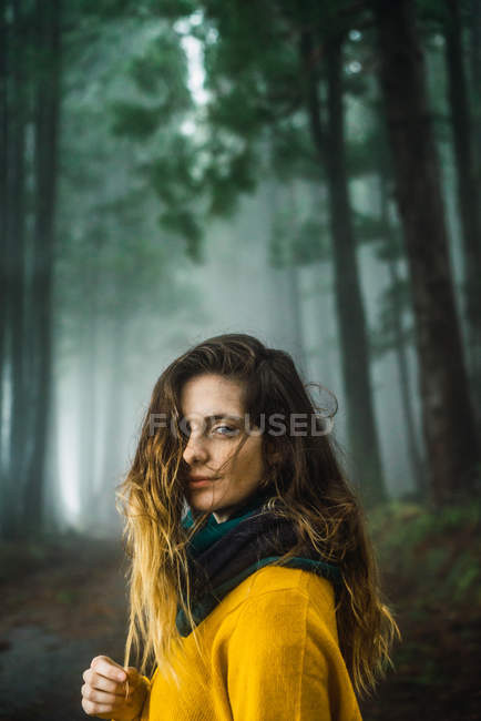 Brunette woman looking at camera in forest — Stock Photo