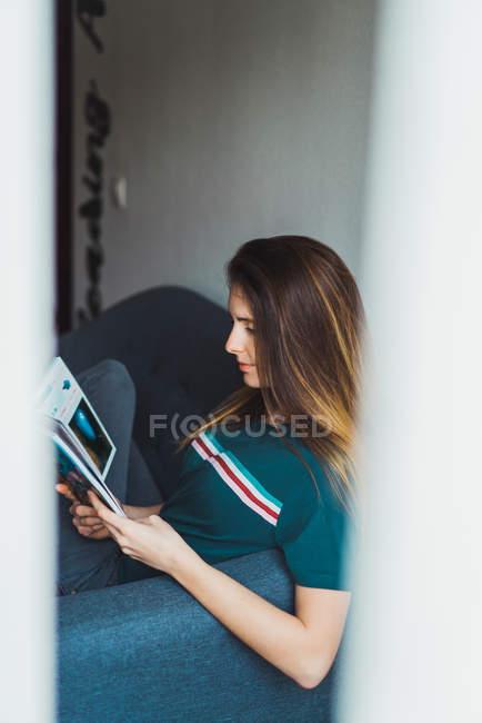 Ragazza che si siede sul divano e scomparto della lettura — Foto stock