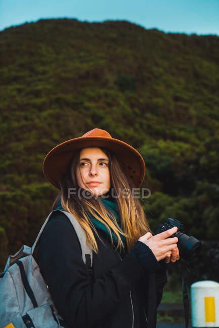 Фотограф позирует с камерой и смотрит в сторону на фоне зеленого леса — стоковое фото