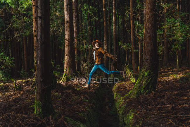 Happy young woman jumping over drain in forest — Stock Photo