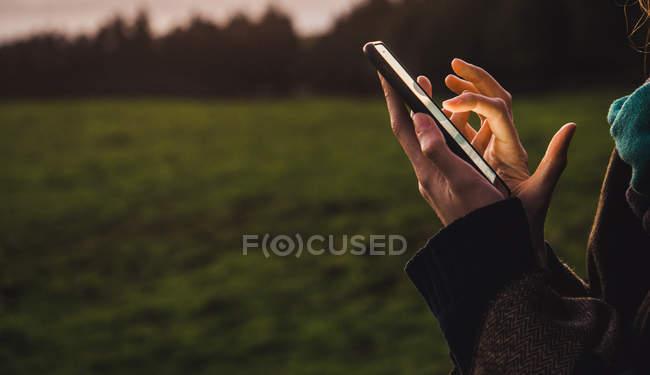 Обрезать женские руки просматривая смартфон на зеленом поле сельской местности — стоковое фото
