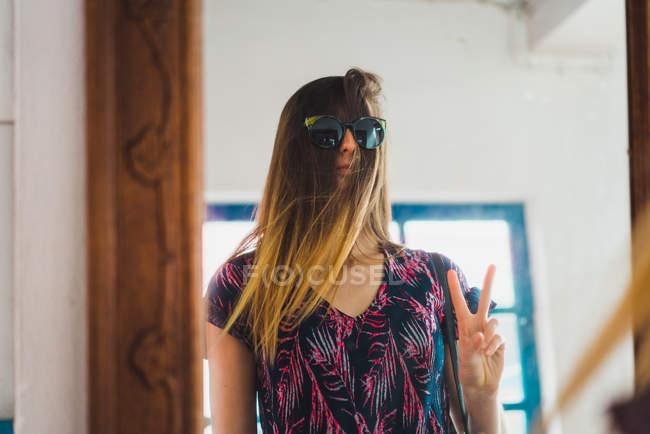 Женщина, стоя на зеркало с очки за волосы и gesturing V-sign — стоковое фото