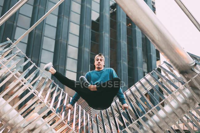 Человек делает акробатические позы в металлической скульптуре — стоковое фото