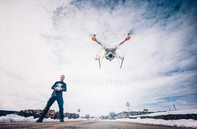 Man flying drone with remote control over scenic cloudscape — Stock Photo