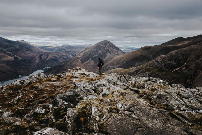 Seitenansicht der Wanderer auf felsigen Hügel im bewölkten Tag stehen. — Stockfoto