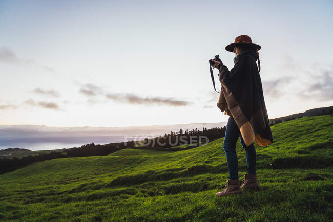 Side view of woman taking shots with camera in green fields — Stock Photo