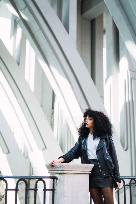 Stylish young curly woman standing and posing at fence in city. — Stock Photo